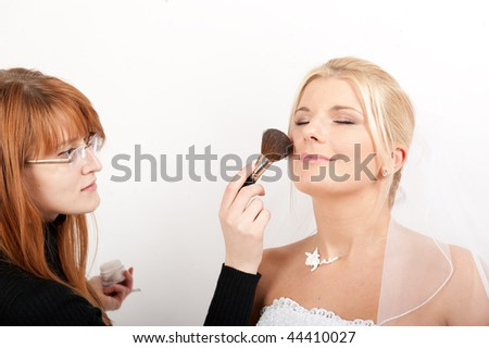 Professional make-up artist preparing young beautiful bride for a wedding applying powder - stock photo