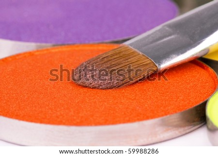 Professional make-up brush on orange eyeshadows round palette, closed-up - stock photo