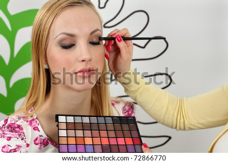 Professional makeup artist applying makeup to attractive young woman face. - stock photo
