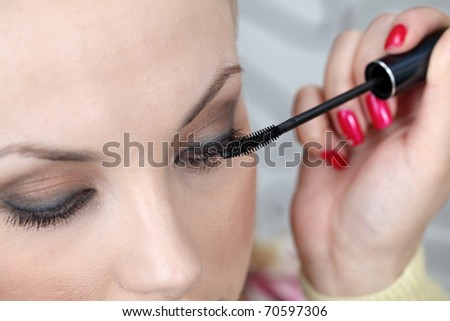 Professional makeup artist applying mascara on the eyelashes of a beautiful girl. Intentional shallow depth of field. - stock photo