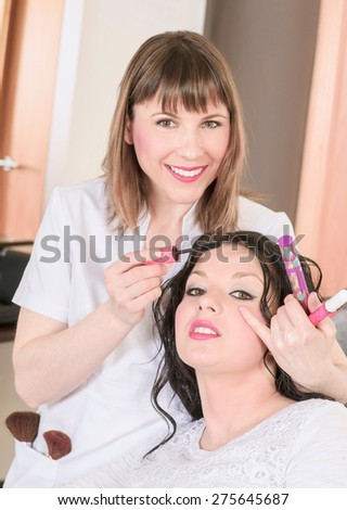 professional makeup making up her client - stock photo