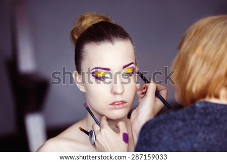 Professional makeup process. Artist is making face style of a young beautiful model at  lilac studio background. - stock photo