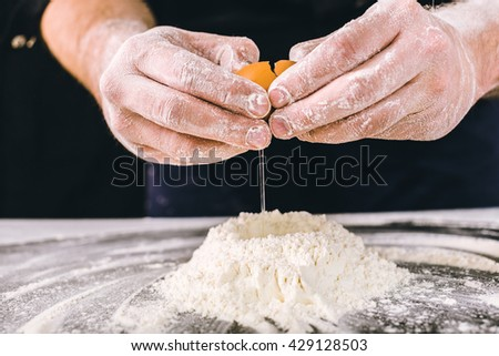 Professional male baker cooking dough with eggs - stock photo