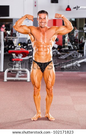 professional male bodybuilder posing in gym - stock photo
