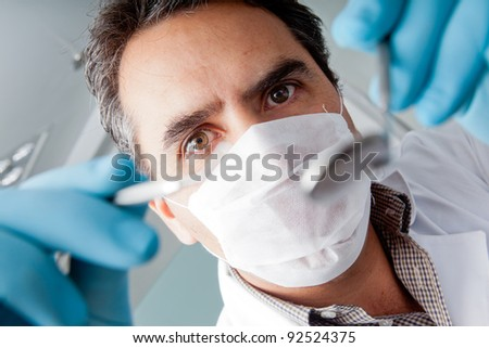 Professional male dentist holding instruments and wearing facemask - stock photo