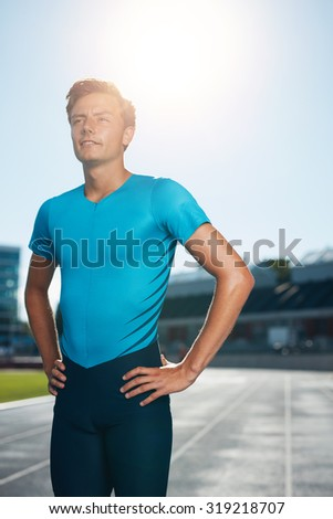 Professional man athlete standing with his hands on hips looking off camera into the distance. Sprinter stands in lane at the athletics track in a outdoor athletics stadium. - stock photo