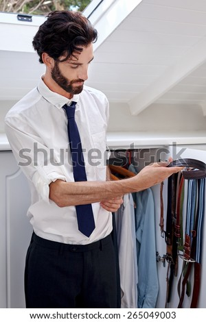 professional man getting ready for work choosing belt from bedroom cupboard - stock photo