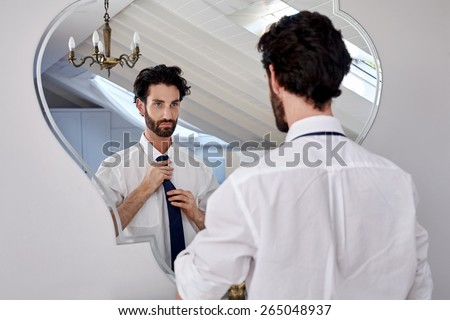 professional man getting ready morning routine shirt and tie in bathroom at home - stock photo