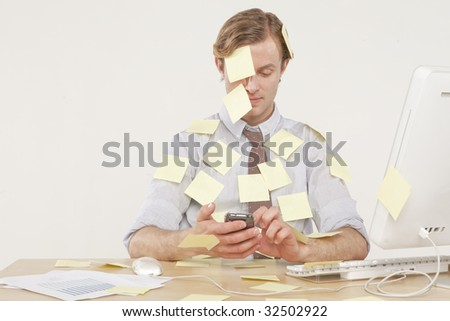 professional man sitting at desk covered in yellow reminder notes - stock photo