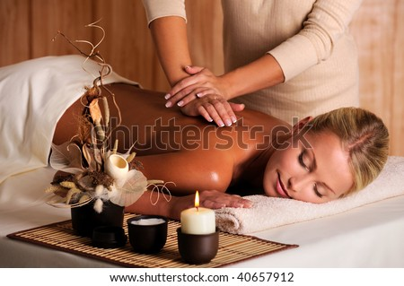professional masseur doing massage of female back in the beauty salon - stock photo