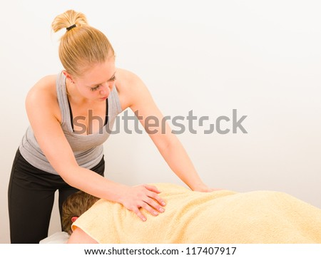 Professional masseur doing massage of male back with a towel - stock photo