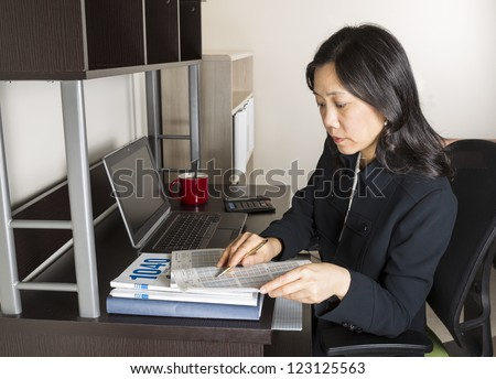 Professional Mature Asian woman  doing income taxes with tax form booklet, calculator, coffee cup and computer on desk - stock photo