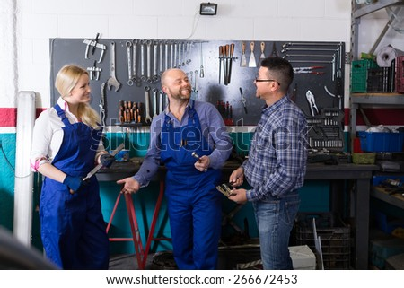Professional mechanics chatting with client at workshop and smiling. Selective focus