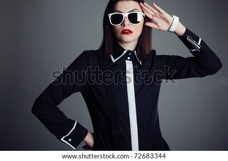 Professional model in black shirt and sunglasses on a gray background - stock photo