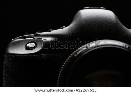 Professional modern DSLR camera low key stock photo/image - Modern DSLR camera with a very wide aperture lens on with highlighted edges against black background - stock photo