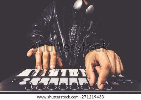 professional musician or DJ hand on studio keyboard synthesizer, isolated on black for dance , groove, remix, underground music background concept - stock photo