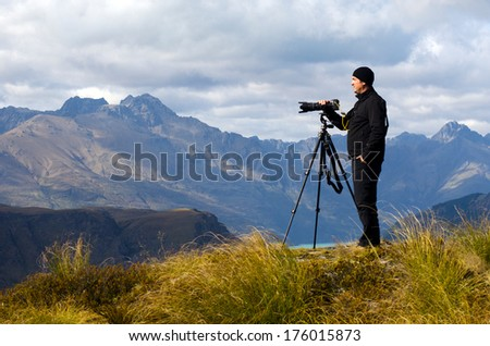 Professional nature and landscape photographer (man) at work outdoor on location. - stock photo