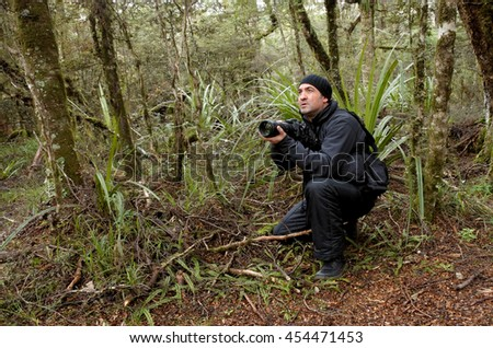 Professional nature, wildlife and travel photographer photographing outdoors during on location photo assignment in Tongariro National Park rain forest, New Zealand. copy space. - stock photo