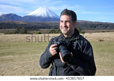 Professional nature, wildlife and travel videographer/photographer photographing  Mount Ngauruhoe outdoors during on location photo assignment. copy space. - stock photo