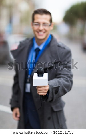 professional news reporter doing interview outdoors - stock photo