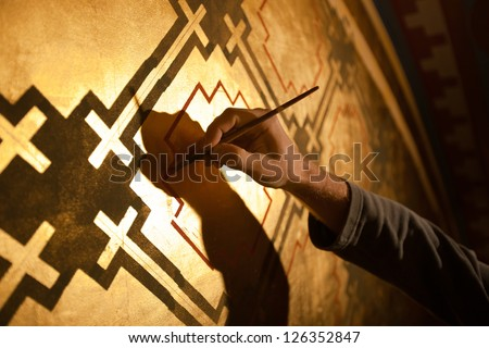 Professional painter restorer  at work, painting a mural - stock photo