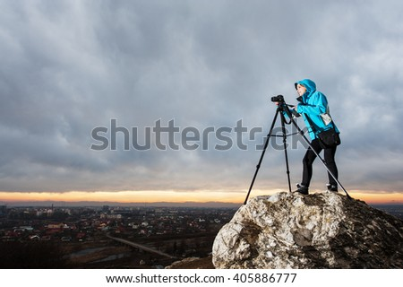 Professional photographer is standing with her camera on tripod on the big rock at city overview point. Woman is taking picture of the landscape. Rain clouds and sunset in the background - stock photo