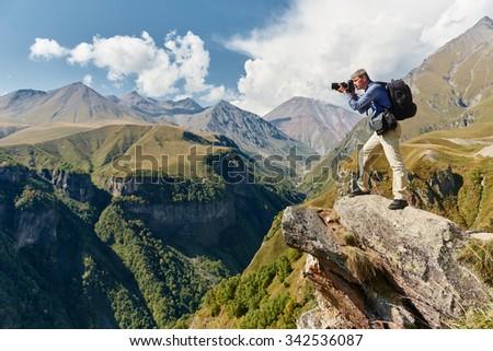 Professional photographer making landscape photos by digital mirror camera at rock mountainon - stock photo
