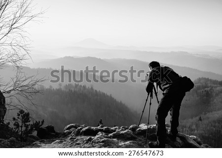 Professional photographer  on location takes photos with mirror camera on peak of rock. Dreamy fogy landscape, spring orange pink misty sunrise in a beautiful valley below. Black and white photo - stock photo