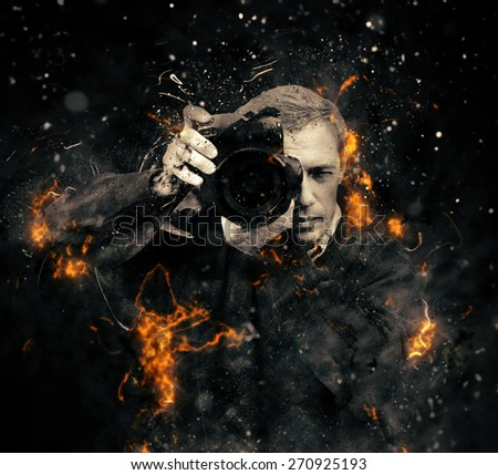 Professional photographer with dslr camera in fire on dark background - stock photo