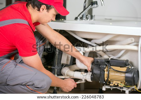 Professional plumber with a wrench. Clogged sink. - stock photo