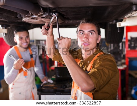 Professional positive young mechanics repairing car of client - stock photo