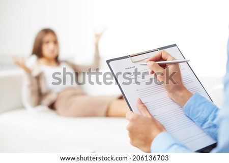 Professional psychiatrist consulting her patient and making notes in application form - stock photo