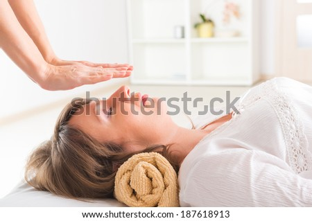 Professional Reiki healer doing reiki treatment to young woman - stock photo