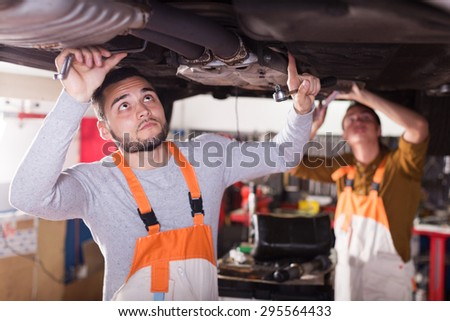 Professional serious mechanics repairing car of client - stock photo