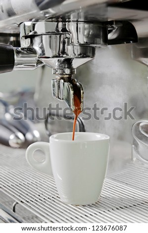 Professional silver gray coffee machine with white cup and pouring drink - stock photo