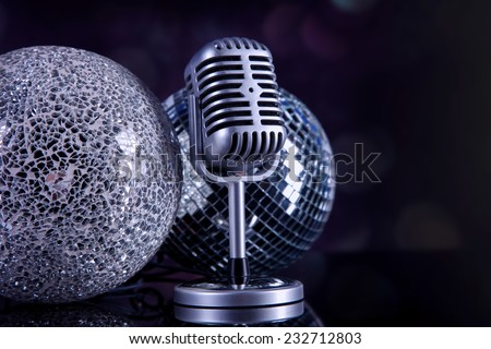 Professional silver microphone on a black glossy background - stock photo