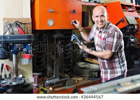 Professional skilful  positive shoemaker heeling footwear on machine in workshop - stock photo