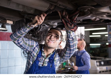 Professional smiling serviceman  repairing car of client - stock photo