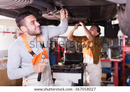 Professional smiling young mechanics repairing car of client - stock photo