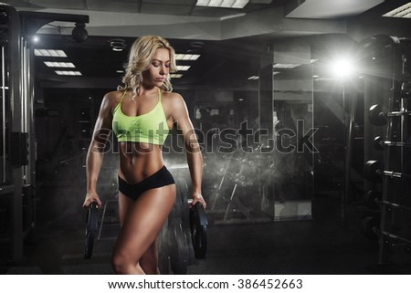 Professional sport fitness woman with weight disk in gym - stock photo