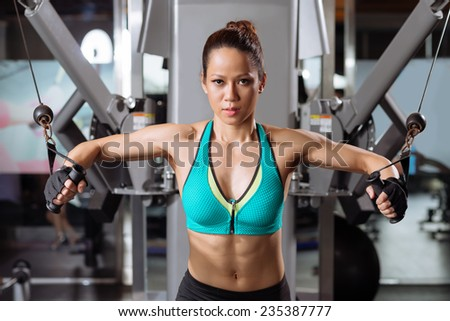 Professional sportswoman lifting weights in the gym - stock photo