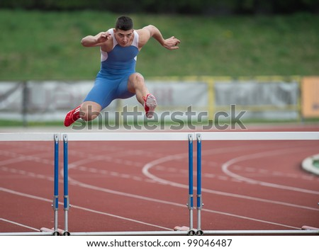 Professional sprinter jumping over a hurdle - stock photo