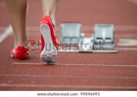 Professional sprinter walking towards the starting line and starting blocks on a running track - stock photo