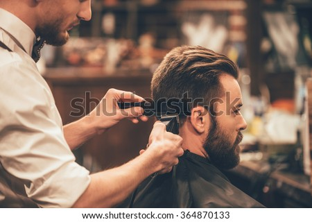 Professional styling. Close up side view of young bearded man getting haircut by hairdresser with electric razor at barbershop - stock photo