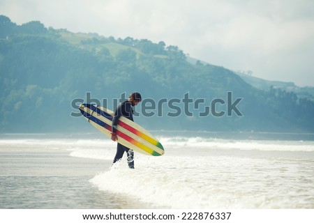 Professional surfer dressed in wetsuit ready to surfing on big waves, young surfer carrying surfboard while walking on the beach and looking at ocean to find the perfect spot for surfing on big wave - stock photo