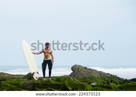 Professional surfer in black wetsuit standing on moss rocks, sexy surfer in wetsuit holding a surfboard and waiting the waves - stock photo