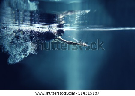 professional swimmer crawl underwater isolated blue background - stock photo