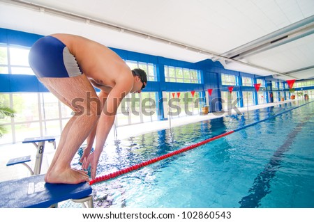 Professional Swimmer getting ready to jump in the swimming pool for practice. - stock photo