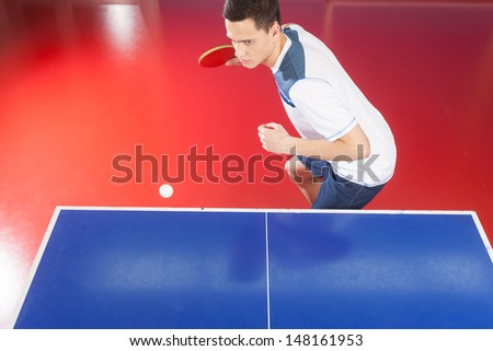 Professional table tennis player. Top view of confident young men playing table tennis - stock photo