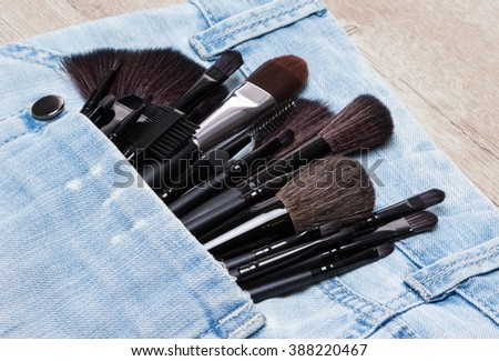 Professional tools of make-up artist in shabby jeans pocket. Sponge tip applicators and makeup brushes: for applying foundation, powder, blush, eyeshadow, eyebrow brushes and others. Selective focus - stock photo